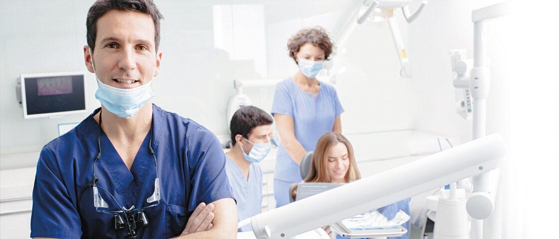 Zahnarzt im Behandlungsraum mit Zahnarzthelfern