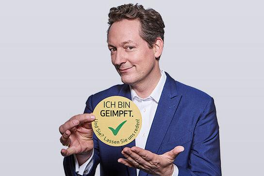 Dr. Eckart von Hirschhausen mit Button der Impf-Kampagne